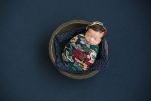 Ensaio Newborn por Ana Kobashi. Representação de uma matrioska sobre fundo azul petróleo.