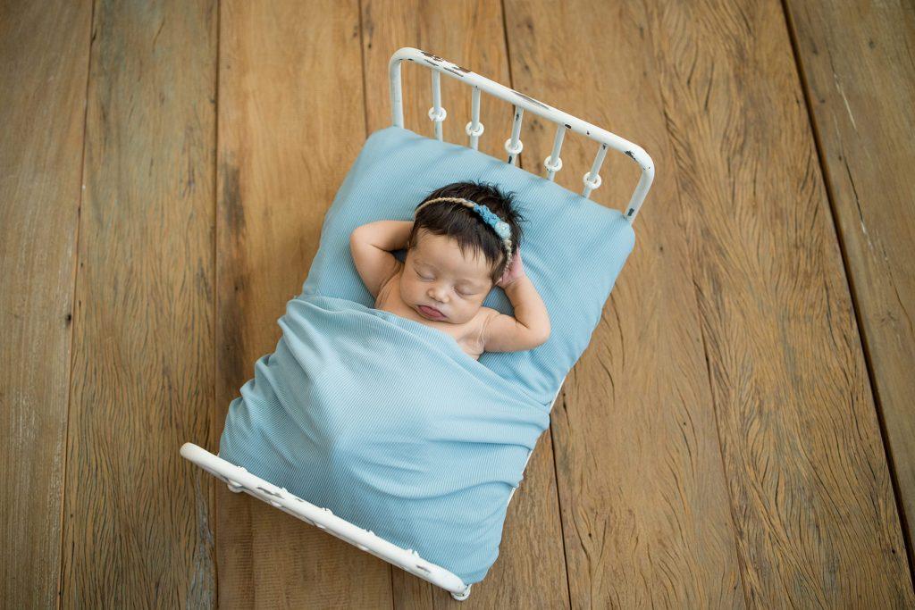 Foto de Ensaio Newborn por Ana Kobashi. Recém nascido em caminha azul.