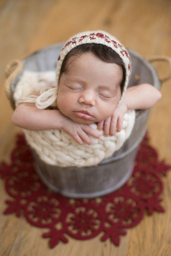 Bebe recém nascido dentro de balde cinza e detalhes natalinos em ensaio newborn por Ana Kobashi